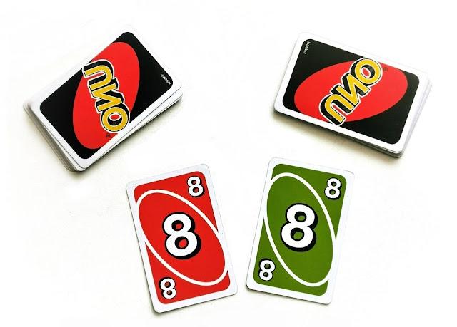 na zdjęciu mamy dwa stosy kart uno oraz dwie odkryte karty czerwoną o wartości osiem i zieloną o wartości 8