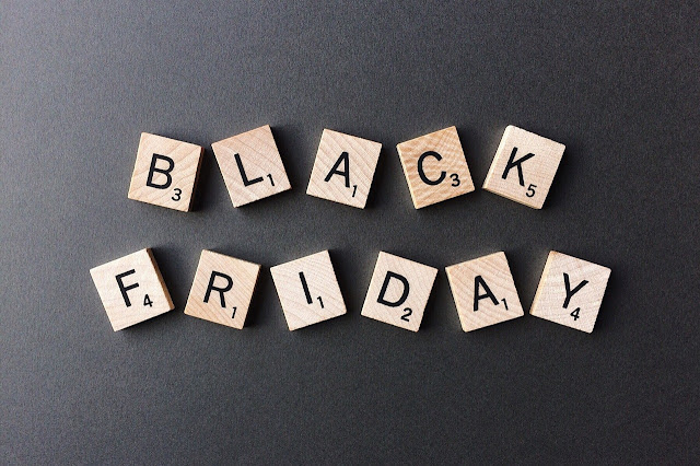 "Scrabble tiles on a black surface spelling ""BLACK FRIDAY"""