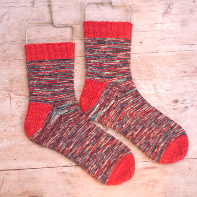 pair of hand knitted sock on sock blockers with contrasting red and a mottled green/red for the main
