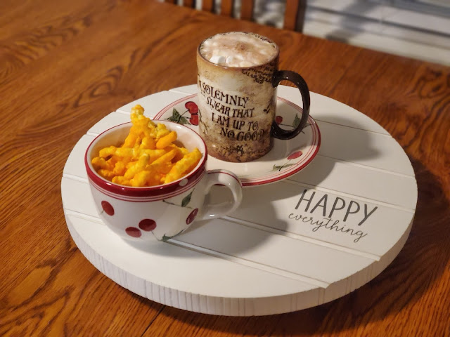 """White Lazy Susan that says """"happy everything"""" in black lettering, on top of a wooden table. On top of the Lazy Susan is a soup bowl with cheetos inside and a Harry Potter coffee cup that says """"I solemnly swear I am up to no good."""" The coffee cup is full to the brim with hot chocolate and mini marshmallows"""