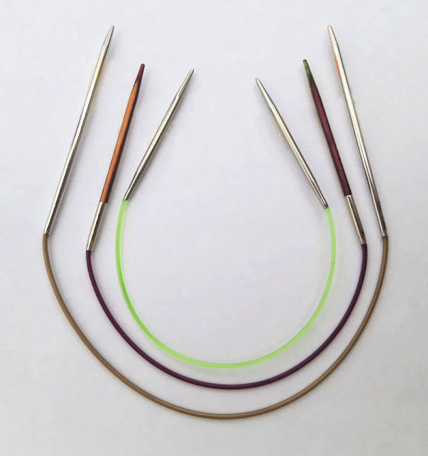 Close up of three short circular knitting needles.  They are arranged in side, largest to the outside and smallest on the inside.  They have different tips (outside and inside are metal whilst the one between is coloured wood) and different coloured cables; gold on the outside, purple in the middle and green in the very centre).