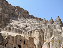 Cradle of pinnacles in various stages of erosion, from cap to shark fin to pinnacle, Cappadocia