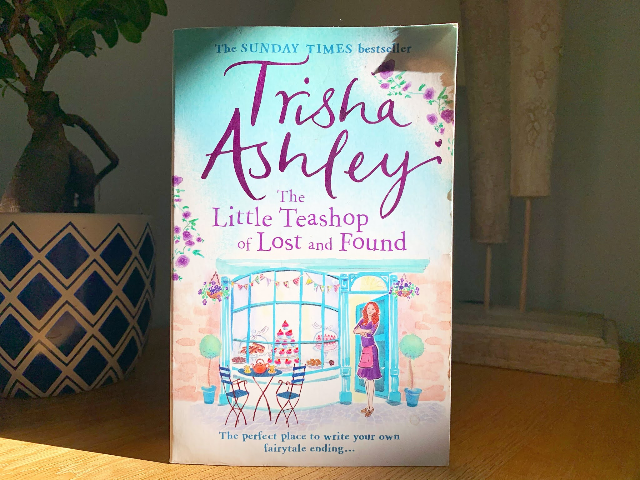 The Little Teashop of Lost and Found by Trisha Ashley on a shelf