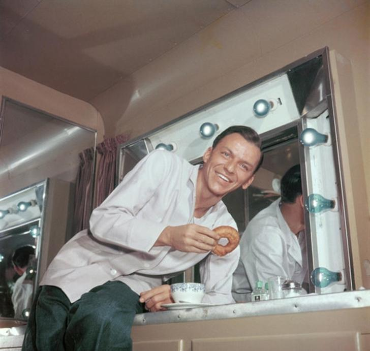 Frank Sinatra drinks coffee with a donut in the dressing room in 1950