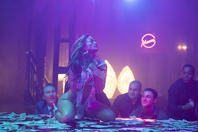 Hustlers 2019 movie still featuring Jennifer Lopez dancing on stage in neon lighting surrounded by tons of money