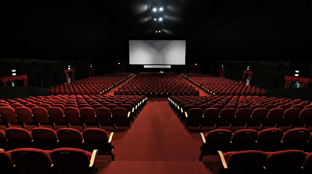 Large, empty cinema with seats and screen