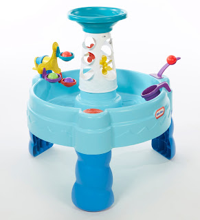 A blue water table with a tower and a number of colourful attachments