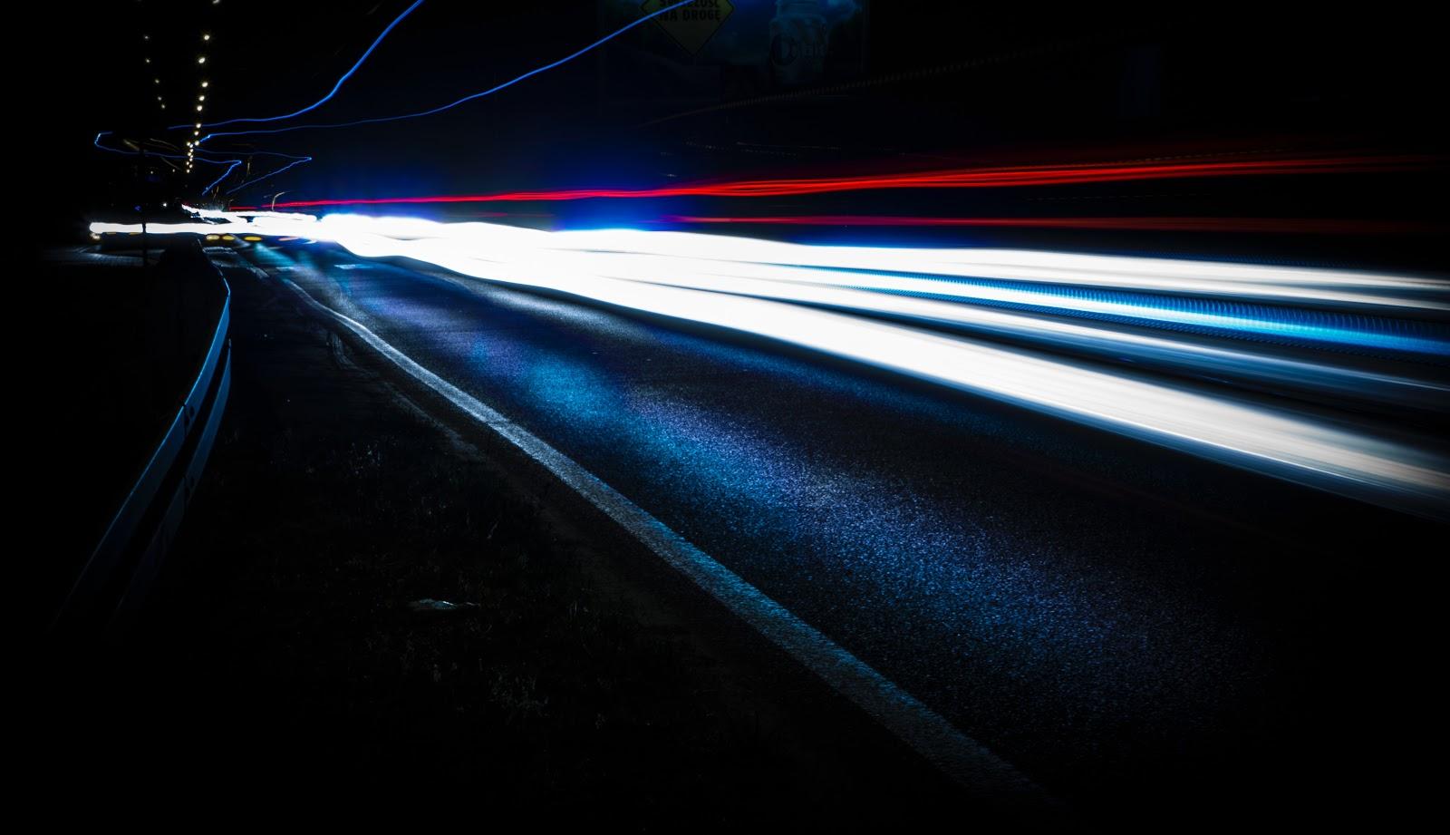 暗闇の道路を走る車の発光