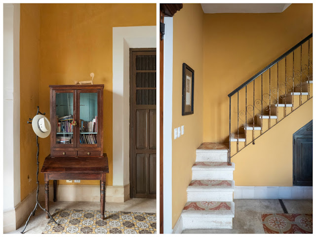 Mueble aparador con perchero y sombrero; y escalera de piedra con pared amarilla