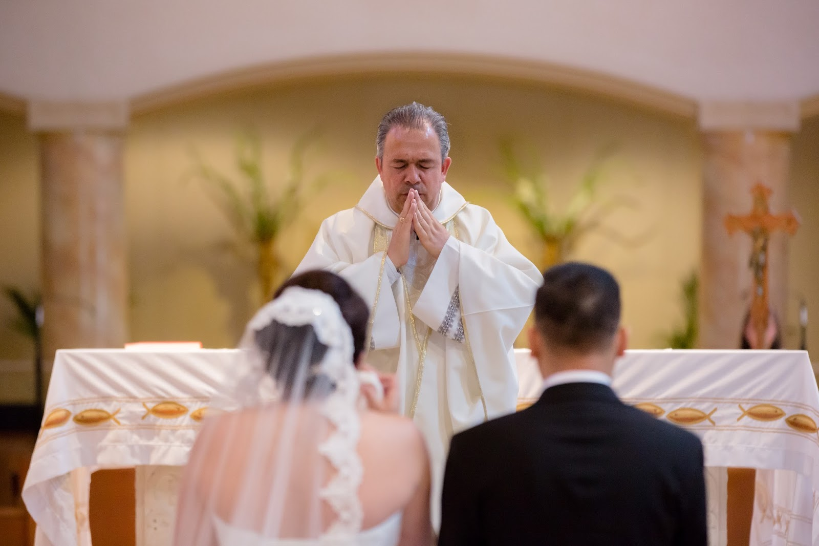 Priest Praying with the Bride and Groom