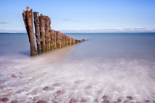 Porlock Weir beach groynes under a blue sky by Martyn Ferry Photography