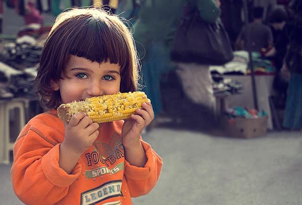 Little kid eating corn, so cute :)