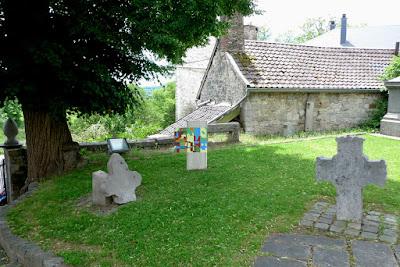 Stèle en béton plantée verticalement dans le sol et peinte avec des fromes colorées aux teintes crayeuses. Un volet en bois est accroché sur la gauche peint avec des formes plus petites.