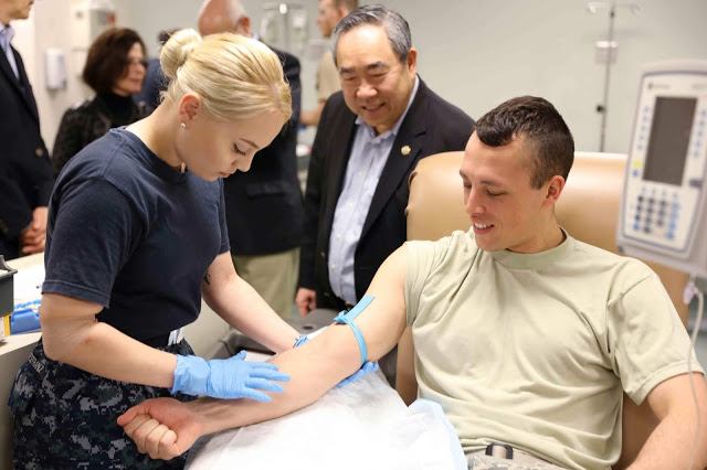 a female puts an IV in a man's arm