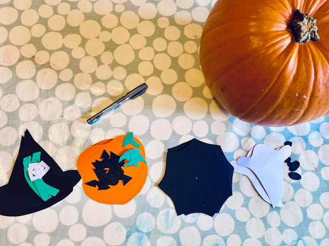 Pieces of card cut and in a row ready to make witches hat, pumpkin, spider webs and ghost which will be hung together to make halloween bunting