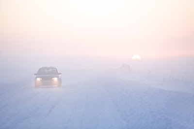 Cars driving with their headlights on during the day during winter in Iceland