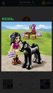 Игрушечные конь и девочка рядом с подарком стоит на дороге