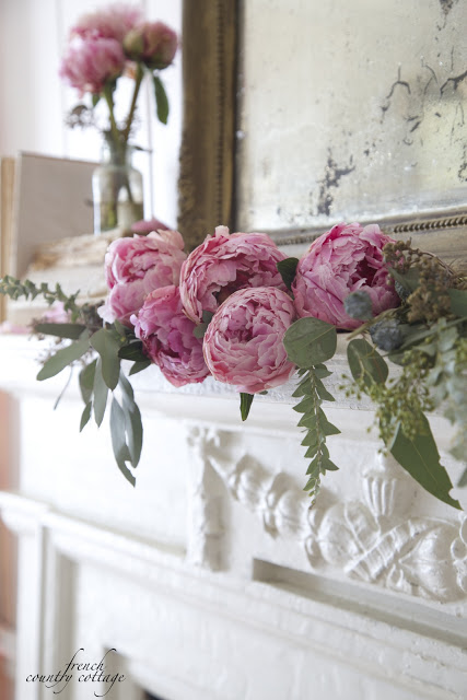 Antique mantel decorated with eucalyptus and peonies