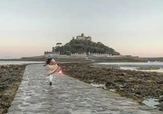 a girl walks across a cobbled causeway, wrapped in a blanket and carrying a lantern. St Michael's Mount and a castle is ahead of her.