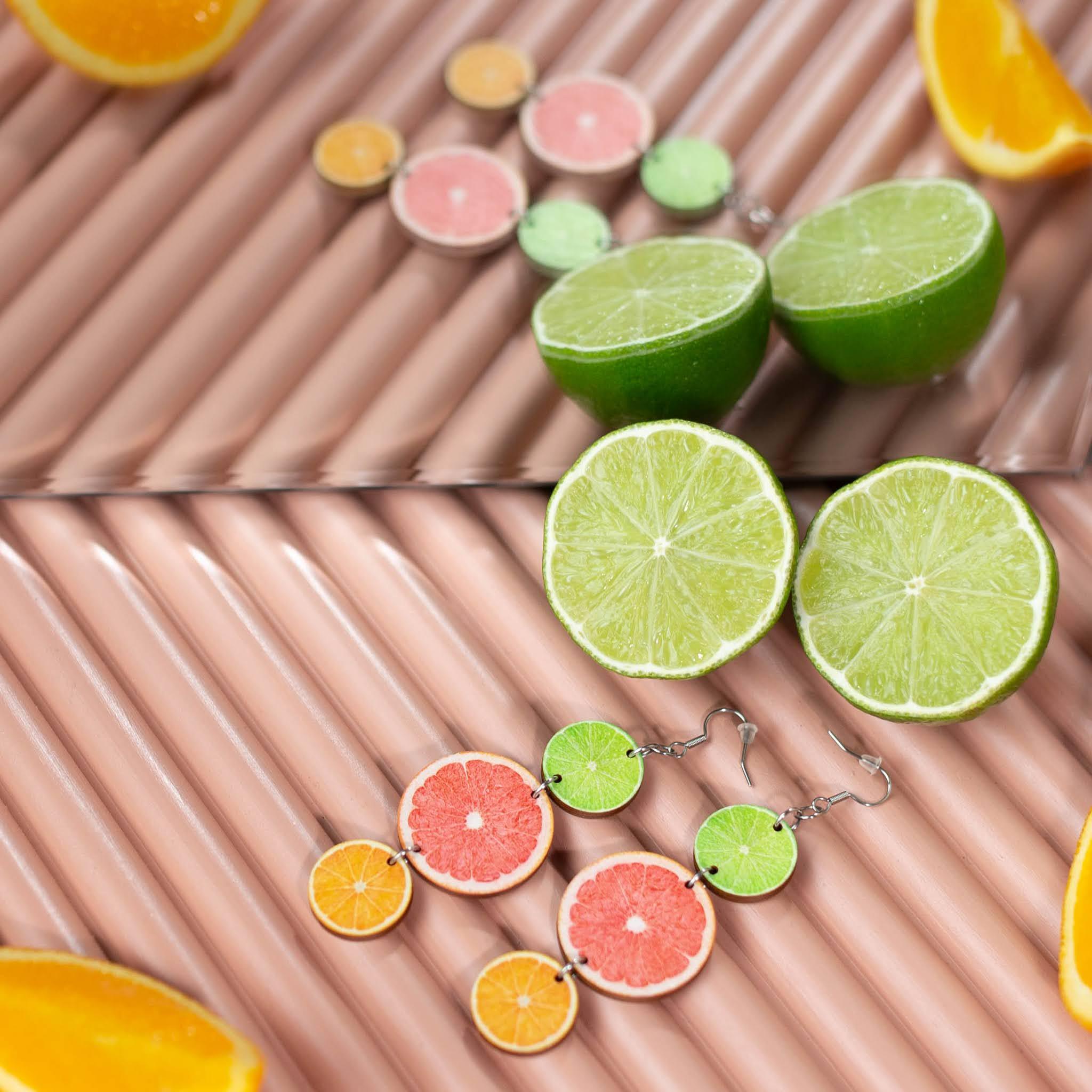 Vaaleanpunaiseksi maalatun sormipaneelin päällä korvakorut sekä appelsiini- ja limelohkoja. Korvakorut ja osa hedelmistä heijastuvat taustan peilistä.