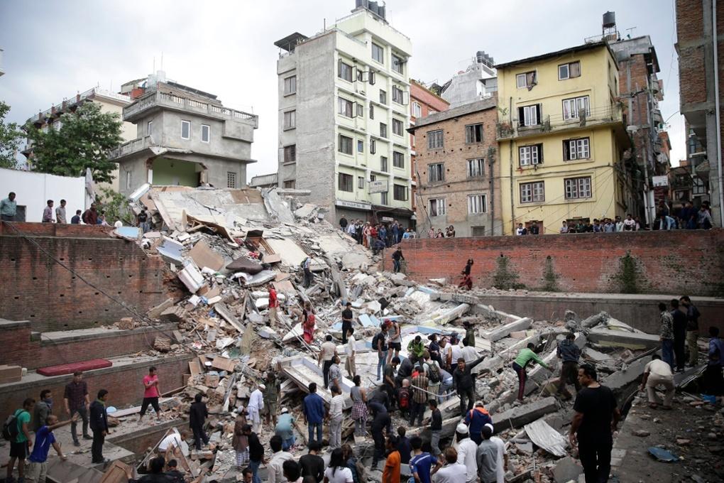 Người ta đang tìm kiếm nạn nhân bị đè dưới đống đổ nát của một tòa nhà ở Kathmandu. Hình bởi Narendra Shrestha/EPA.