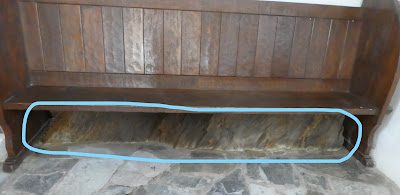 Wooden pew with bare rock visible underneath