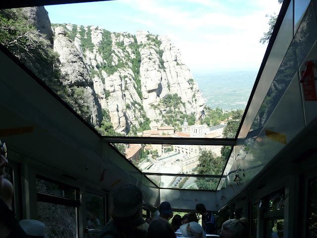 Через прозрачную крышу фуникулера видно уплывающий вниз монастырский комплекс Монсеррат