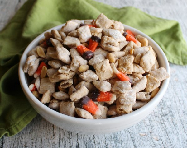 close bowl of white chocolate puppy chow mixed with candy corn and peanuts to make squirrel chow snack mix