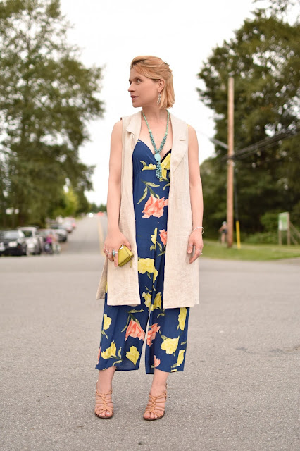 styling a floral jumpsuit with a sleeveless linen coat and strappy nude sandals