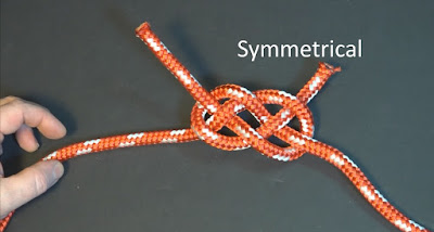 symmetrical Carrick Bend flat knot in red and white braided nylon rope