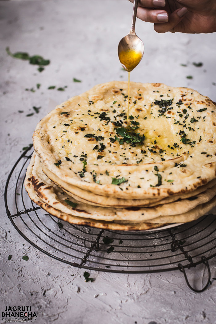 RESTAURANT STYLE GARLIC AND CORIANDER NAAN is soft, fluffy brushed with garlic flavoured flatbread which is easy to make at home with using staple ingredients such as plain flour, yeast, yogurt and milk. Perfect with Indian curries.