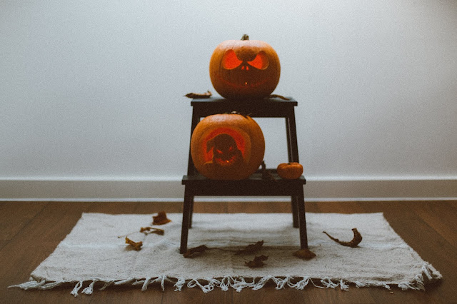 lit carved pumpkins on stand