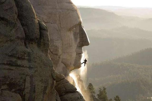 Un trabajador escalando una de las cabezas de 18 metros del Monte Rushmore (Kärcher-Instagram/La Vanguardia)