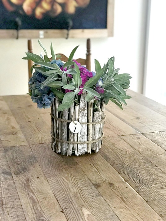 Driftwood vase and sage flowers on a wooden table