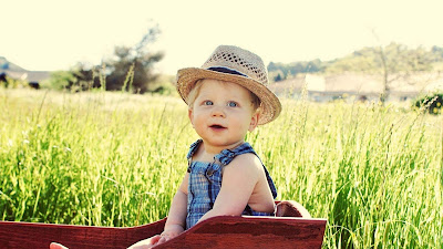smiling-babu-with-hat-sitting-in-the-farm-pics