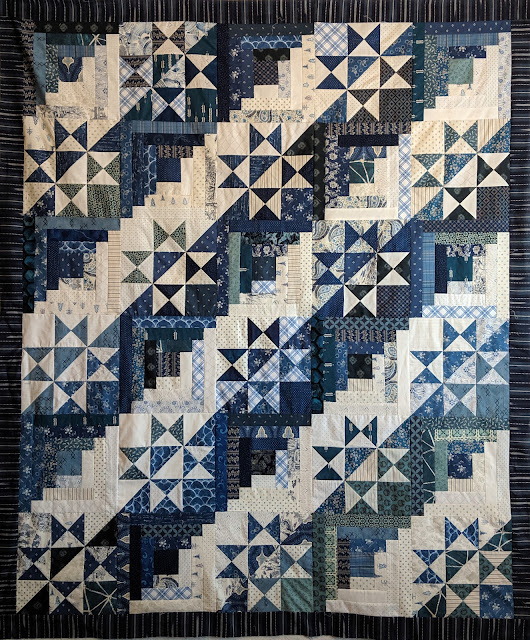 Alternating blue and white Ohio Star and Log Cabin blocks with a navy ikat border
