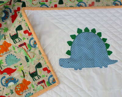 Handcrafted stegasaurus applique baby quilt with flannel dinosaur back and hand sewn binding