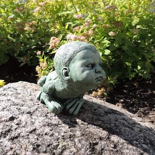 Creepy frog boy stone statue