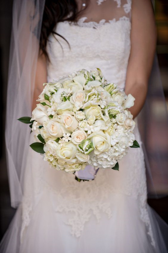 classic bridal bouquet features white and cream roses hydrangeas