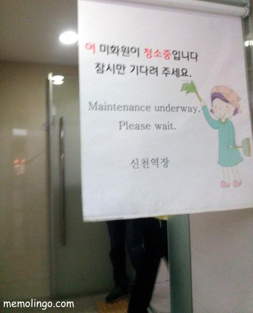 Mensaje en coreano avisando de que una señora está limpiando el aseo masculino