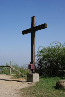 Das Gipfelkreuz der Glessener Höhe. An der Vorderseite hängt ein roter Holzkasten in dem sich das Gipfelbuch befindet.