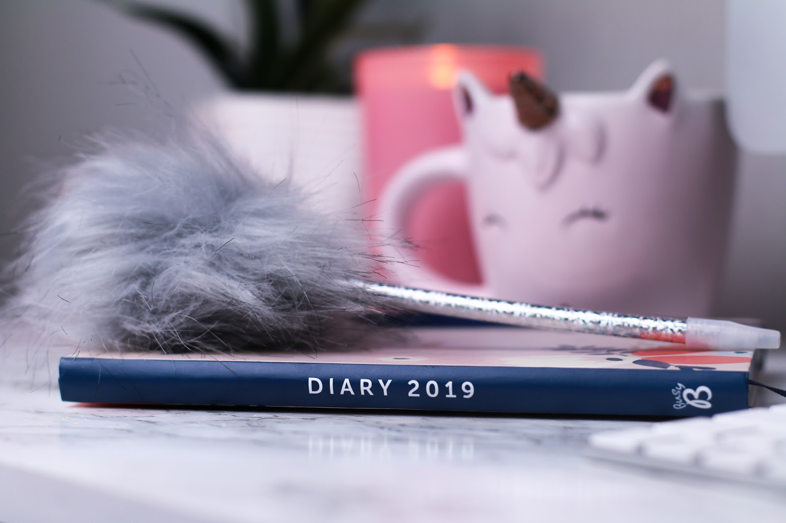 a busyb 2019 diary on a marble counter top with a grey fluffy pen on top of it. There is a white unicorn light in the background and a pink candle.