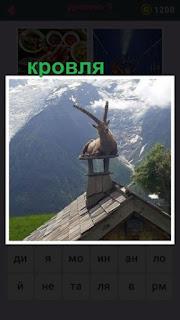 на кровле на трубе сидит коза на фоне гор и олаков