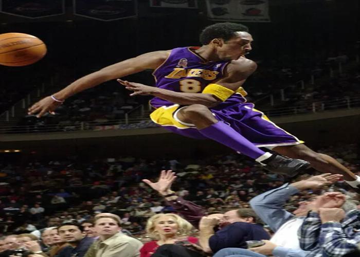 Pemain Los Angeles Lakers, Kobe Bryant melompati deretan penggemar setelah menyelamatkan bola saat bertanding melawan Houston Rockets di Houston pada 20 Desember 2001. Kobe Bryant memenangkan lima gelar juara NBA dan peraih medali emas Olimpiade dua kali