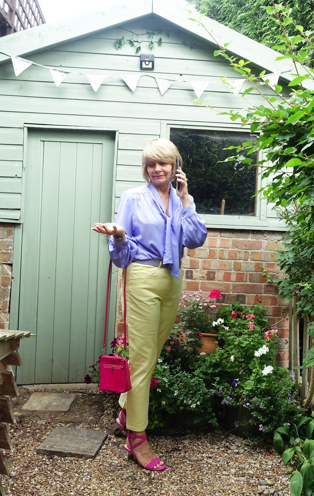 Over 50s blogger Gail Hanlon from Is This Mutton in a lilac blouse with yellow trousers and pink accessories