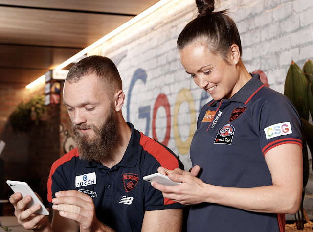 Image of AFL players on their mobile phones