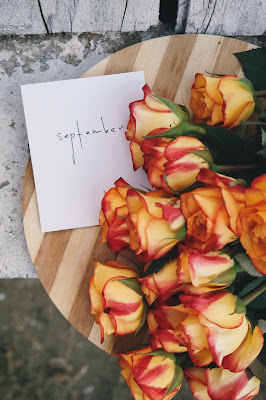 "Yellow and red roses on a two-toned wooden table with a white envelope that says ""September"". Photo by Brigitte Tohm on Unsplash"