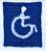 International Access Symbol (white wheelchair symbol on a blue background) created with crochet by Jodiebodie using a freeform technique to create the shapes and finished with a white crab stitch border.