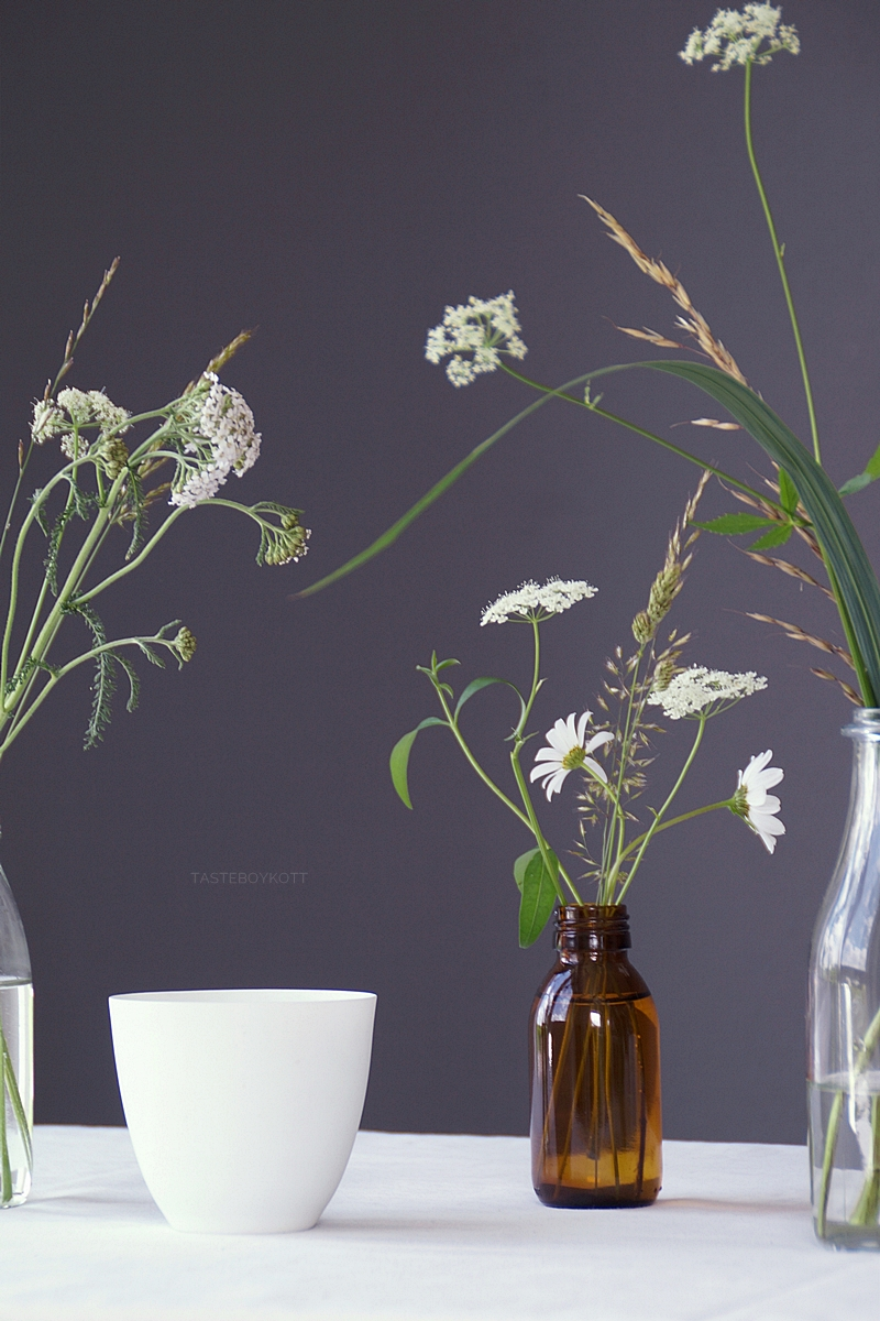 Simple and quick table decoration idea for summer with white wildflowers in vintage glass bottles as vases