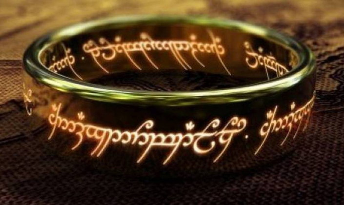 Imagem: fundo com um mapa escrito a mão, e o Um Anel, um anel de ouro com vários escritos em élfico, uma letra inclinada e fina, cheia de curvas e brilhando.